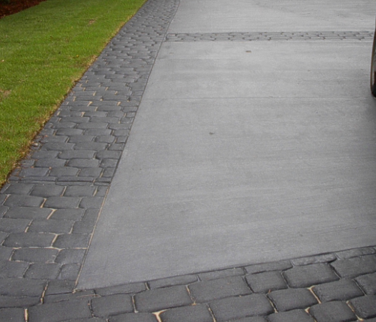 Concrete driveway with a stamped cobblestone edging around whole driveway.
