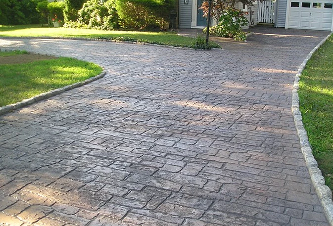 Stamped concrete driveway with concrete edging along both sides of driveway.