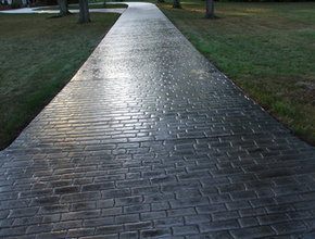 Long driveway with a gray brick stamped design performed by Lansing stamped concrete.