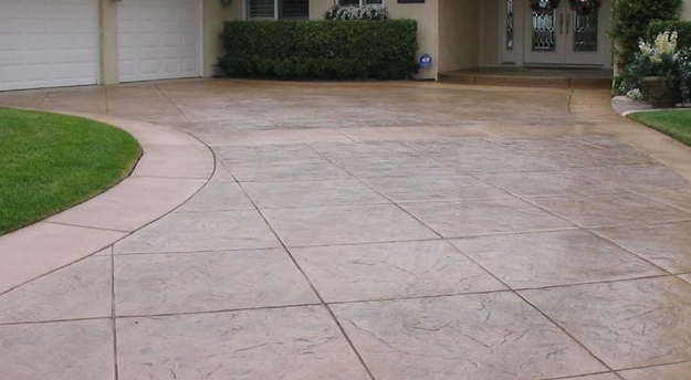Stained concrete driveway with a reddish brown color in Mason, Michigan.